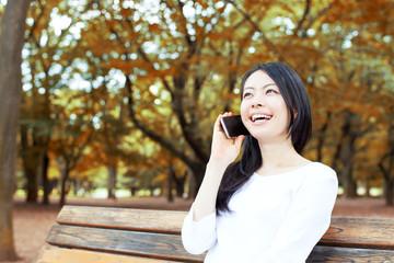 公園で電話をかける女性