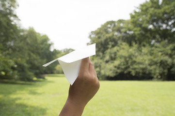 Hand throwing a paper airplane in the air