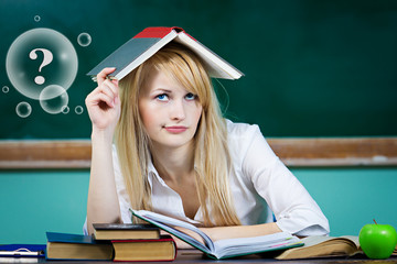 Student sitting at desk in classroom, confused, thinking
