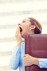 Sleepy young business woman, running to work yawning