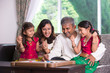 Indian family playing carrom game at home. Parents and children - 70015725
