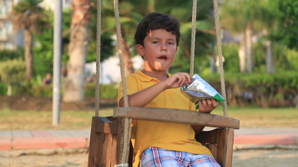 Sad lonely boy eating chips on swing