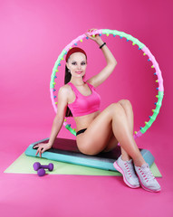 Healthy Lifestyle. Woman Sitting on Mat with Fitness Equipment