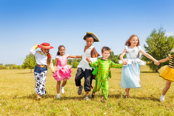 Running kids wearing costumes outside in field