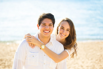 Smiling couple by the sea on sunny summer, autumn day