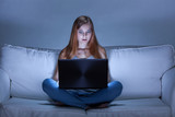 Shocked girl using facebook at night