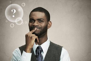 Headshot man thinking, deciding something grey background