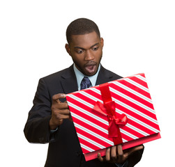 Surprised businessman about to open unwrap red gift box