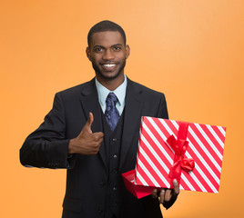 Smiling business man holding present giving thumb up