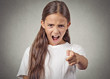 Angry teenager girl screaming pointing finger at you
