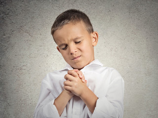 Praying child boy hopeful for best isolated grey wall background