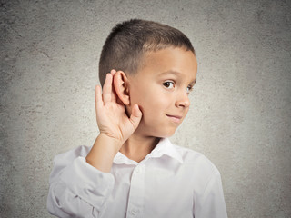 Curious man, boy, listens hand to ear gesture, grey background