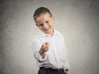 Boy laughing, pointing with finger at someone camera