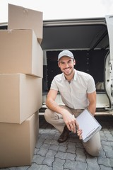 Delivery driver smiling at camera with pile of packages