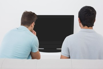 Two soccer fans watching tv