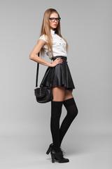 Beautiful woman is in fashion style in black mini skirt.