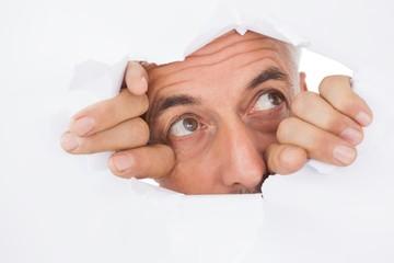 Man peeking through torn white surface