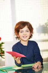 Kind bastelt Wunschzettel für Weihnachten