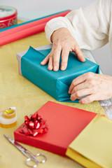 Alte Hände verpacken Geschenk für Weihnachten