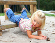 Little girl fell to sand on a playground.