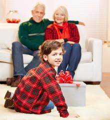 Enkel öffnet Geschenk zu Weihnachten
