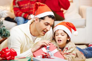 Vater und Sohn packen Geschenke aus an Weihnachten