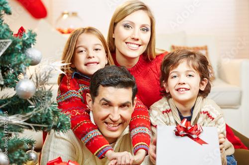 canvas print picture Familie mit Geschenk zu Weihnachten