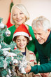Großeltern schmücken Weihnachtsbaum mit Enkel