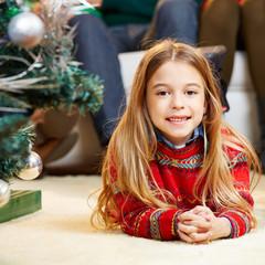 Mädchen liegt zu Weihnachten im Wohnzimmer
