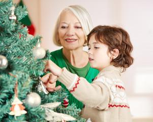 Großmutter und Enkel schmücken Weihnachtsbaum zu Weihnachten