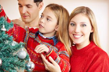 Eltern schmücken Weihnachtsbaum mit Tochter zu Weihnachten