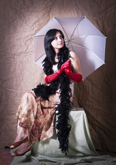 Брюнетка с зонтом и в боа позирует