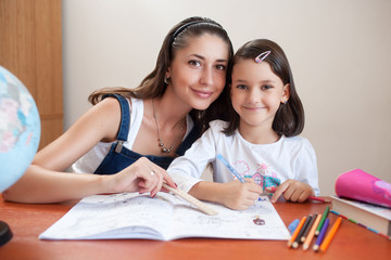 Portrait of a smiling mother with her daughter at her desk