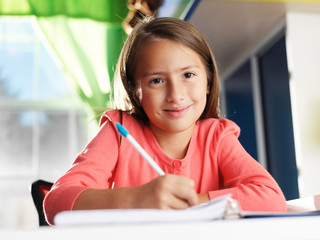 little girl doing home work smiling