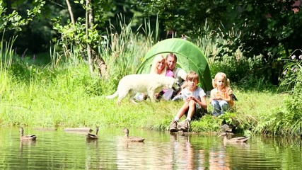family of four camping by the lakeside