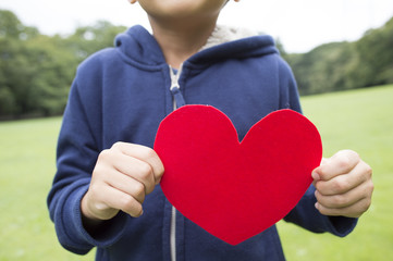Boy holding a red heart