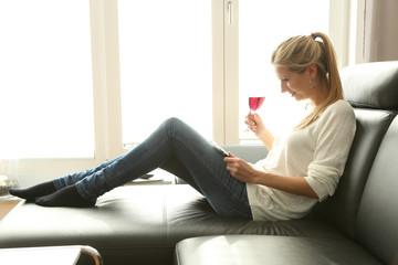 Frau sitzt mit tablet PC und einem Glas Wein auf der Couch