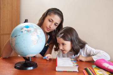 mother shows daughter the country on the globe of the world
