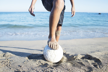 Boy play soccer on the beach