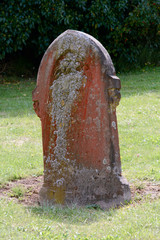 Gravestone covered in red and yellow lichen
