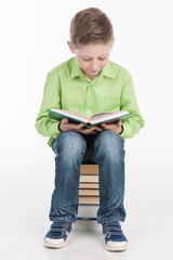 Small boy reading book on white background.