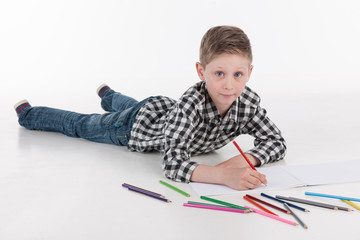 boy lying on floor and drawing pictures.