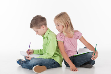 cute little children sitting on floor and drawing.