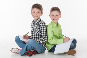 two cute boys sitting on floor drawing.