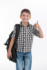 Happy schoolboy wearing backpack and giving thumbs up.