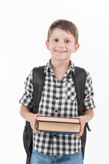 Happy schoolboy wearing backpack and holding books.