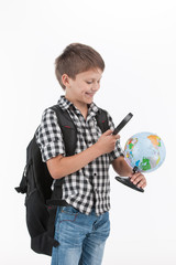 Happy schoolboy wearing backpack and holding magnifying lens.