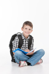 Happy schoolboy with notebook isolated on white background.