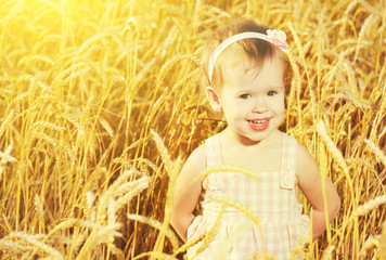 happy little girl in a field of golden wheat in the summer