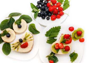 tasty cheesecakes decorated by strawberry, blueberry and mint